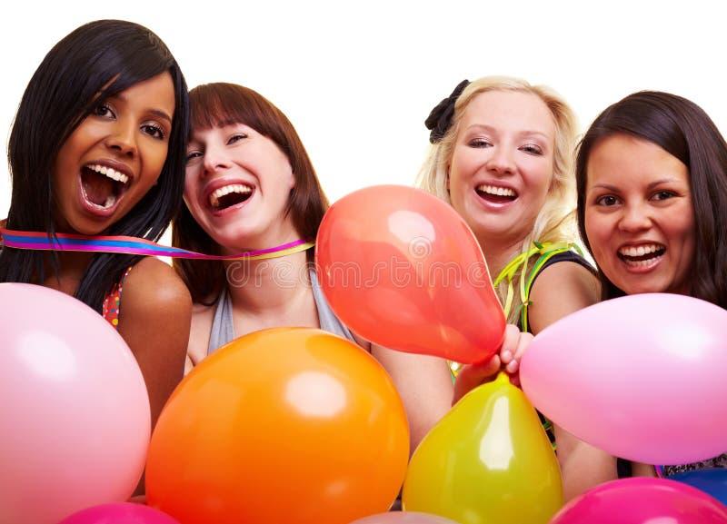 Quatro mulheres felizes que sorriem no partido fotografia de stock
