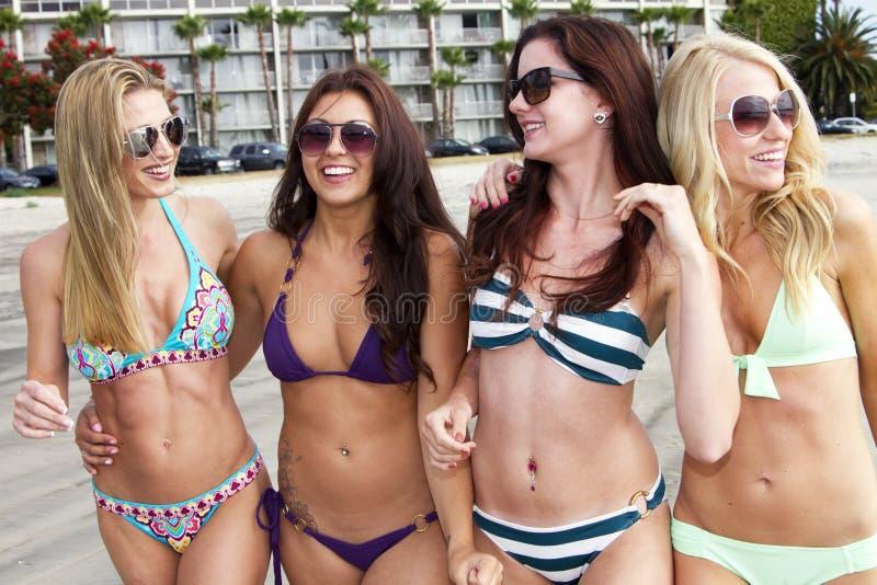 Quatro mulheres novas bonitas que apreciam a praia imagens de stock