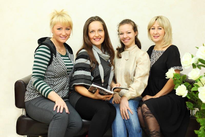 Quatro mulheres sentam-se no sofá de couro preto imagens de stock royalty free
