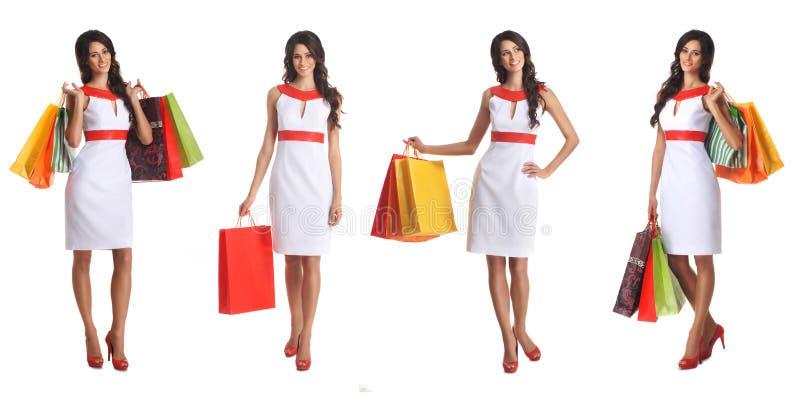 Quatro mulheres triguenhas novas com sacos de compra fotos de stock royalty free