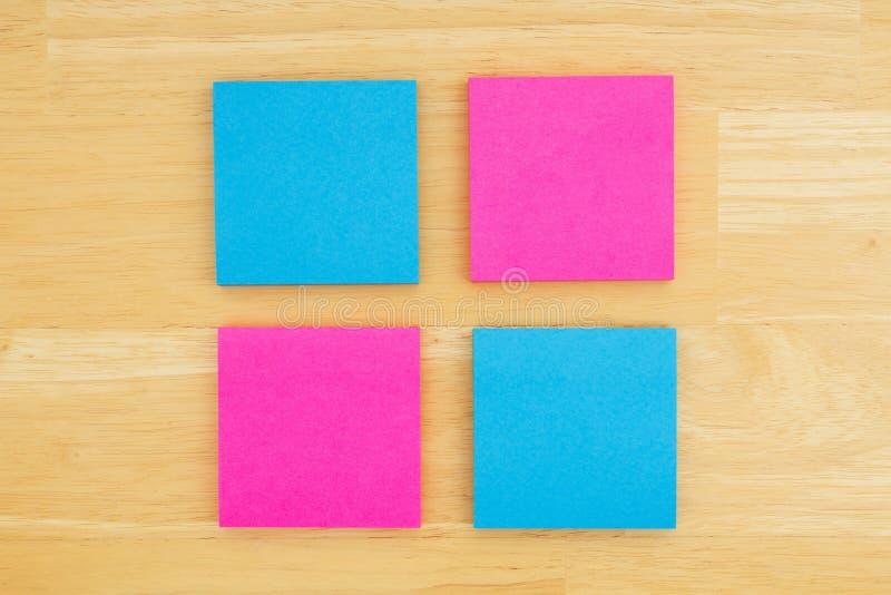 Quatro notas pegajosas vazias em fundo textured da madeira da mesa fotos de stock
