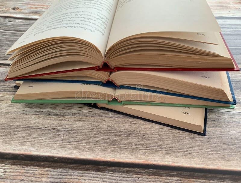 Quatro novelas abertas e sobrepostas em uma tabela de madeira foto de stock