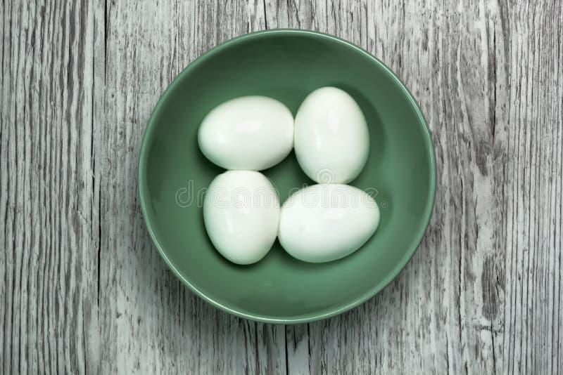 Quatro ovos cozidos em uma bacia em uma vista superior de madeira cinzenta imagem de stock royalty free