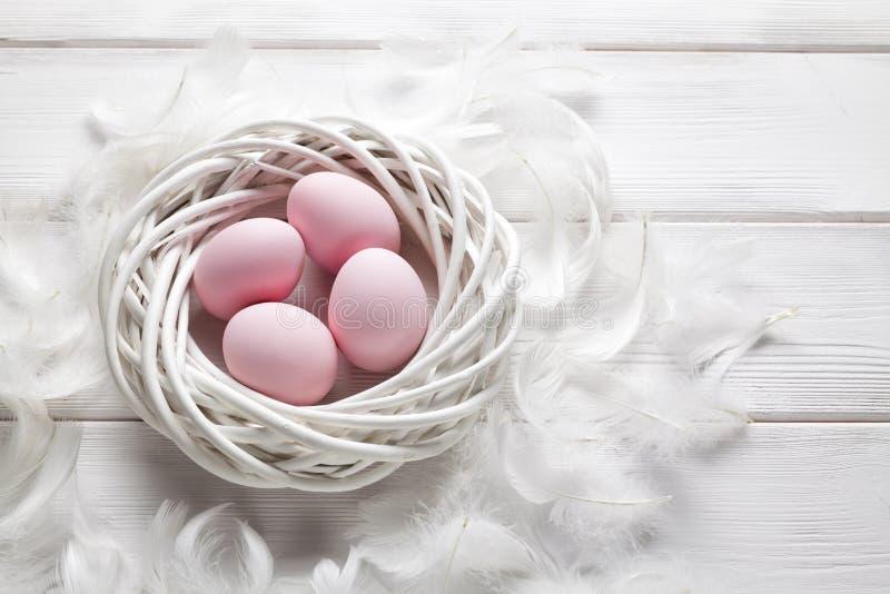 Quatro ovos da páscoa cor-de-rosa no ninho e nas penas brancos imagem de stock royalty free
