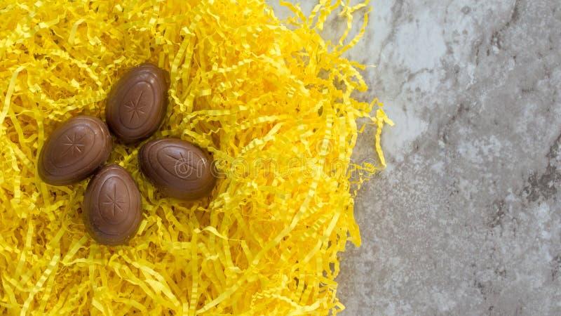 Quatro ovos da páscoa do chocolate na grama amarela da Páscoa em um contador de mármore imagens de stock