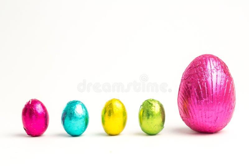 Quatro ovos da páscoa pequenos ao lado do grande fotos de stock