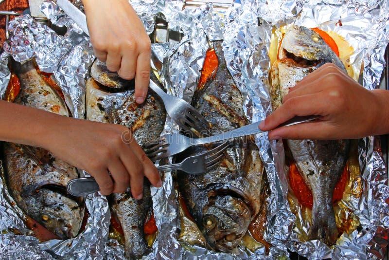 Quatro peixes cozidos do dorado na folha com vegetais para um jantar do feriado da família, as mãos das crianças com forquilhas p fotos de stock