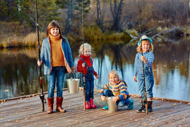 Quatro peixes da captura das meninas em um pontão de madeira Fim de semana no lago Pesca com amigos imagens de stock royalty free