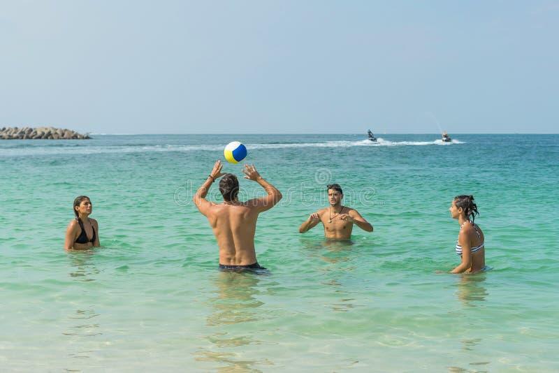 Quatro povos novos do divertimento estão jogando o voleibol na praia na costa de Dubai Emoções humanas positivas, sentimentos, al fotografia de stock royalty free