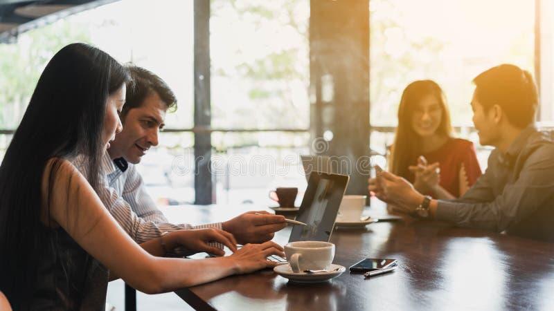 Quatro povos que encontram-se e discutem na cafetaria, trabalho autônomo s foto de stock