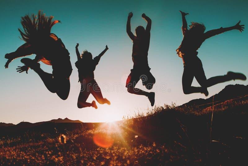 Quatro povos que saltam sobre o céu no por do sol fotos de stock