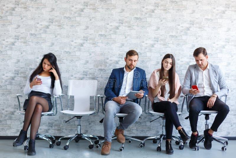 Quatro povos, sentando-se perto de uma parede de pedra e usando um telefone celular dentro fotografia de stock
