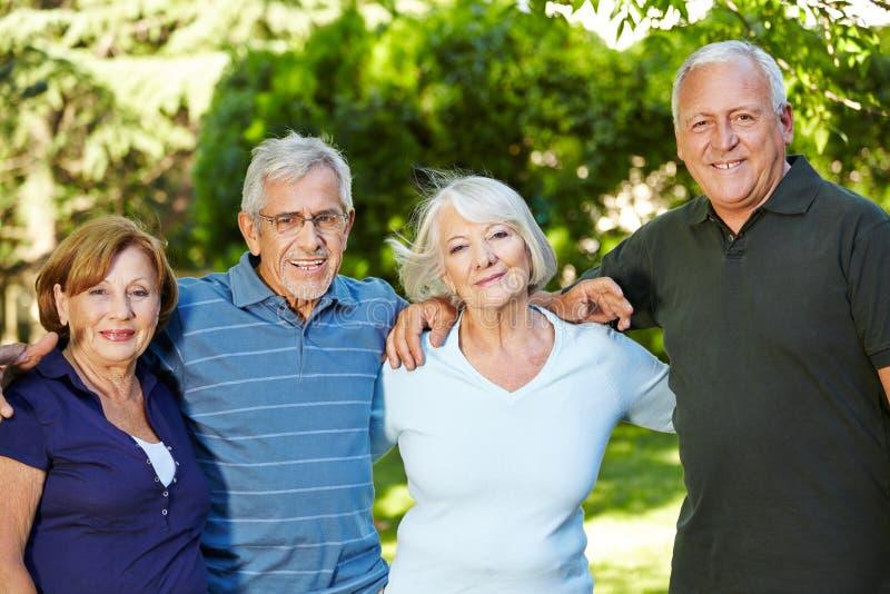 Quatro povos superiores felizes na natureza foto de stock