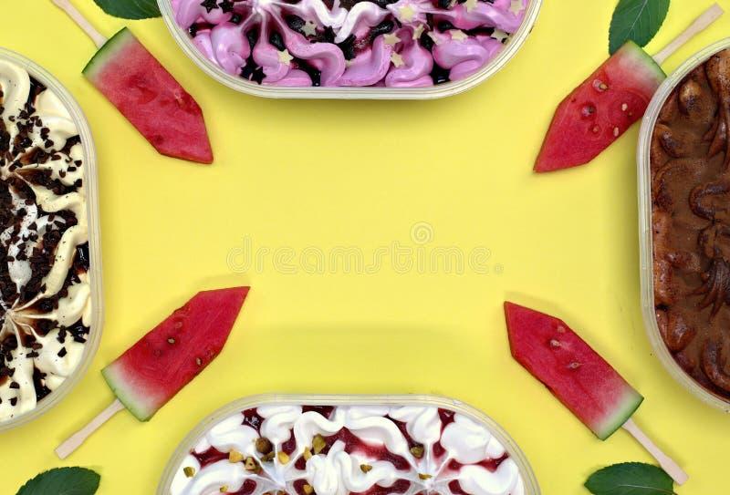 Quatro recipientes com gelado e a melancia coloridos com varas foto de stock