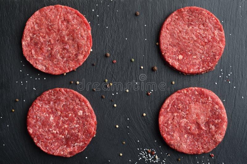 Quatro rissóis pretos principais crus frescos do hamburguer da carne de Angus imagem de stock