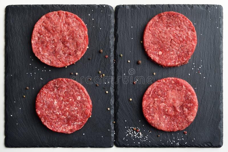 Quatro rissóis pretos principais crus frescos do hamburguer da carne de Angus foto de stock