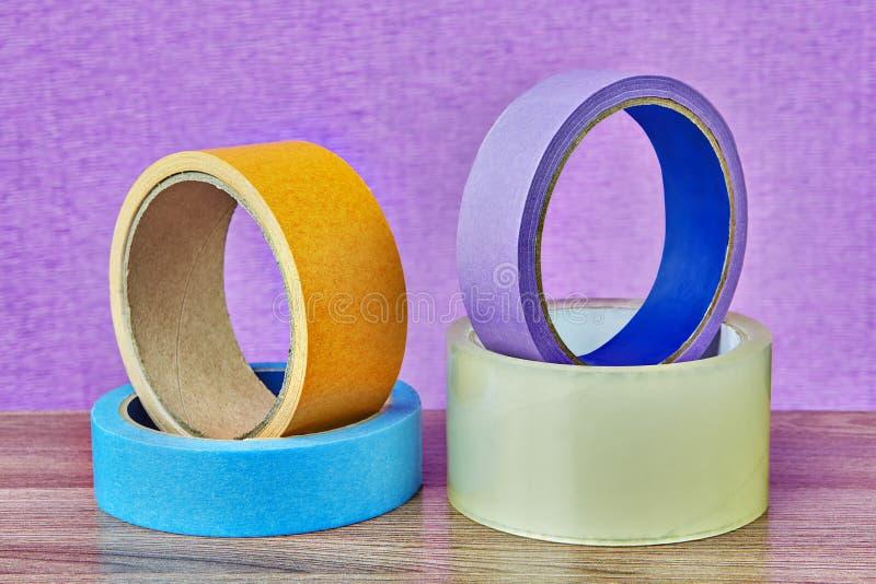 Quatro rolos da fita adesiva que encontram-se na tabela, fundo lilás fotos de stock royalty free