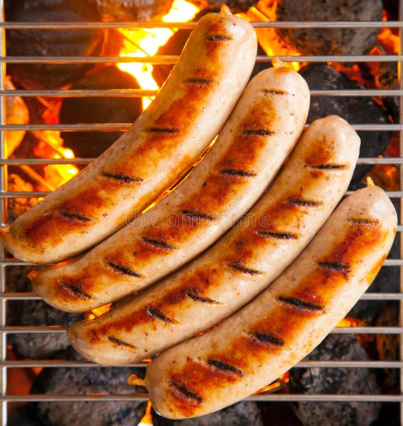 Quatro salsichas chamaram a bratwurst, grelhando sobre carvões quentes em um BBQ fotografia de stock