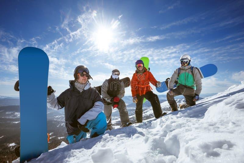 Quatro snowboarders na inclinação do esqui imagens de stock