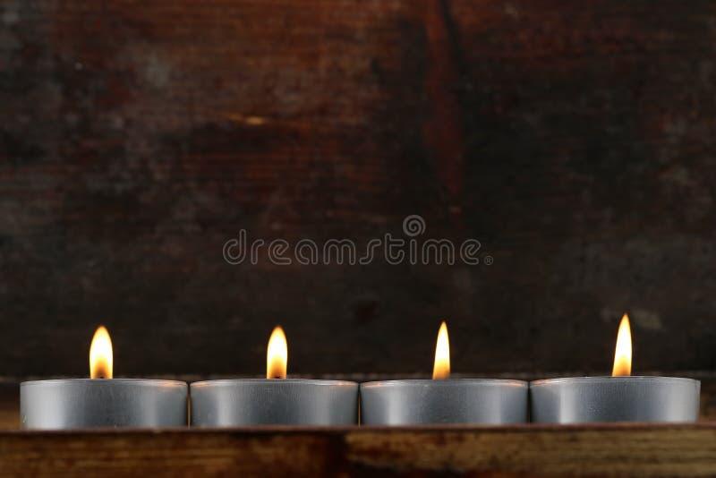 Quatro tealights, velas no fundo de madeira escuro fotos de stock royalty free