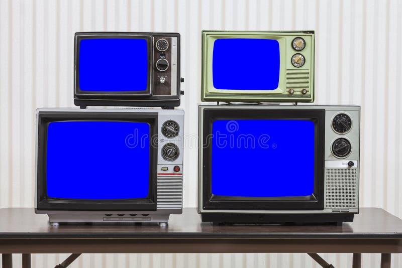 Quatro televisões do vintage com as telas azuis da chave do croma imagem de stock royalty free