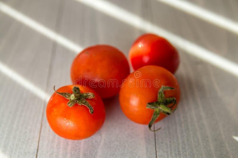 Quatro tomates orgânicos vermelhos na tabela de madeira branca foto de stock