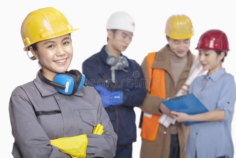 Quatro trabalhadores da construção contra o fundo branco, foco no trabalhador da construção fêmea de sorriso foto de stock royalty free