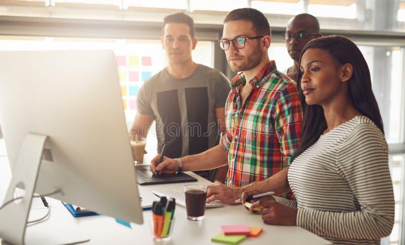 Quatro trabalhadores novos que estão em torno do computador imagens de stock