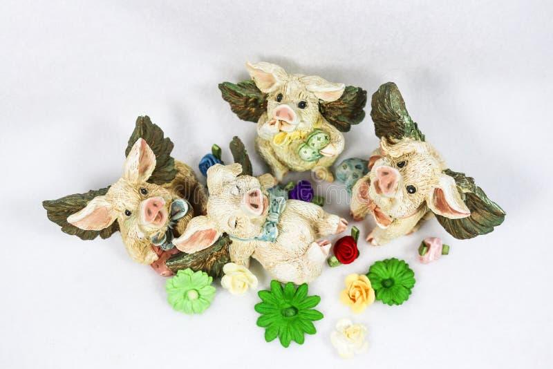 Quatro Valentine Pigs de voo feliz com corações encontram-se ao redor em um campo das flores - vista superior fotografia de stock royalty free