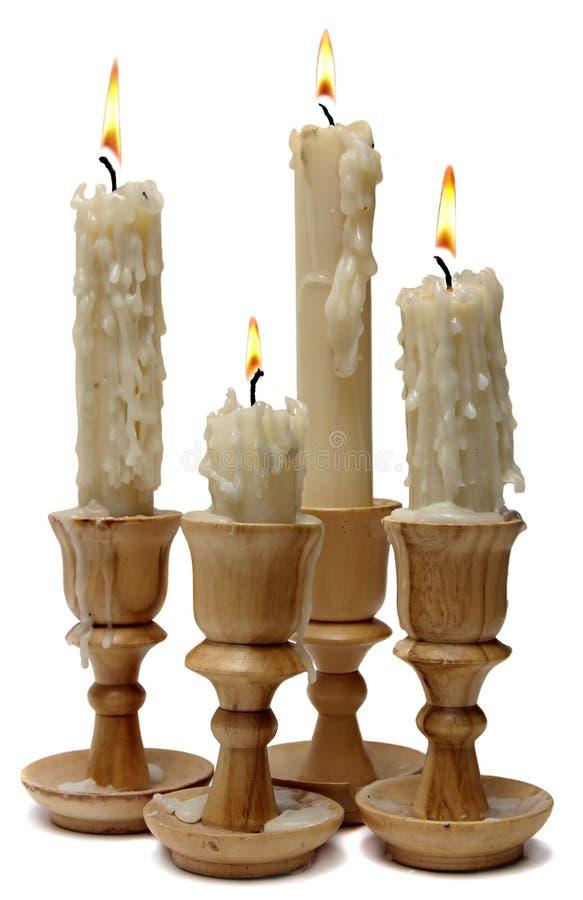 Quatro velas ardentes em castiçal de madeira fotos de stock