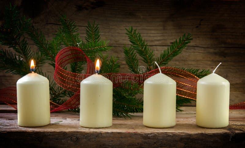 Quatro velas brancas, dois deles que queimam-se no segundo advento, de foto de stock
