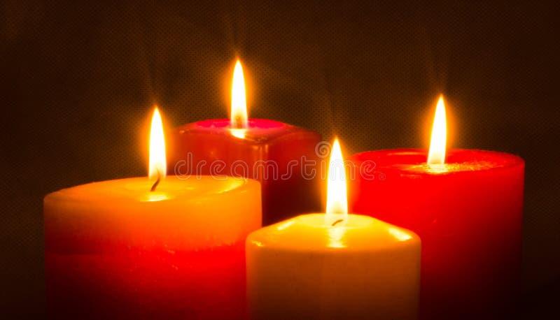Quatro velas coloridas que queimam-se na obscuridade foto de stock