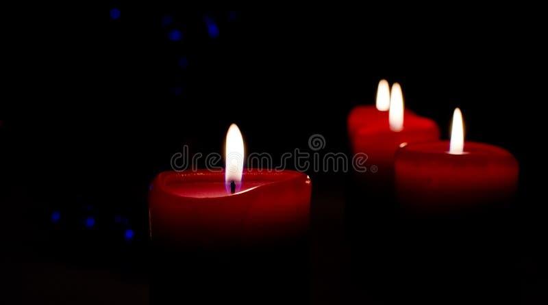 Quatro velas do Natal no fundo preto com bokeh azul imagens de stock