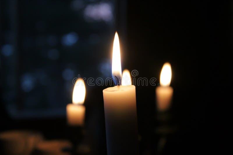 Quatro velas que queimam-se na obscuridade fotografia de stock royalty free