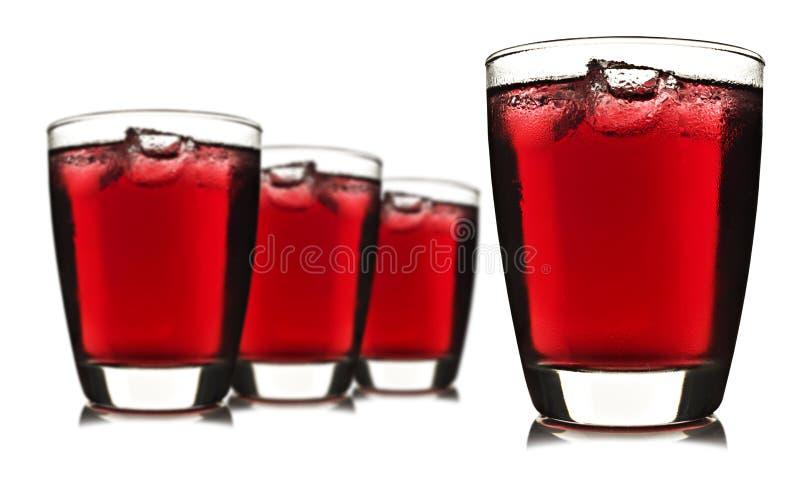 Quatro vidros do suco de fruta vermelho com gelo fotos de stock