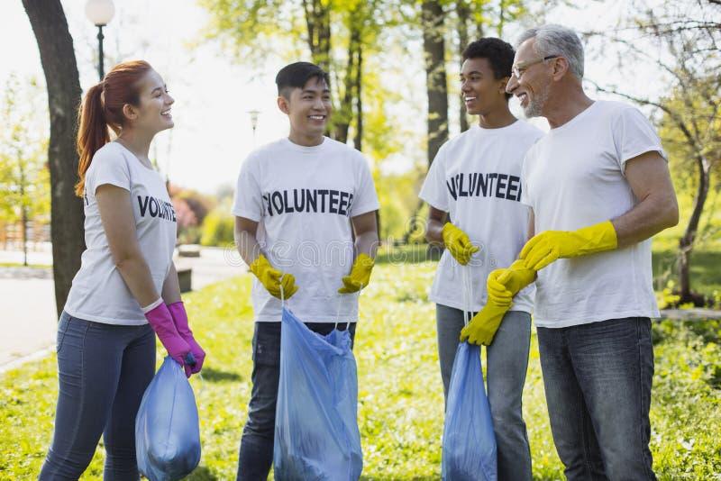 Quatro voluntários joviais que admiram o trabalho imagens de stock