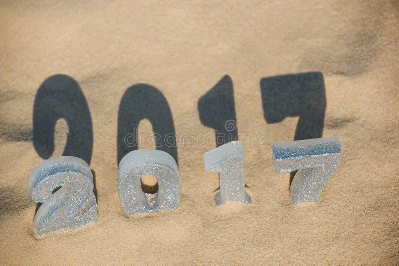Quatro Year& novo x27; as figuras de s estão na areia na praia ou o beira-mar, moldou uma grande sombra na terra imagem de stock