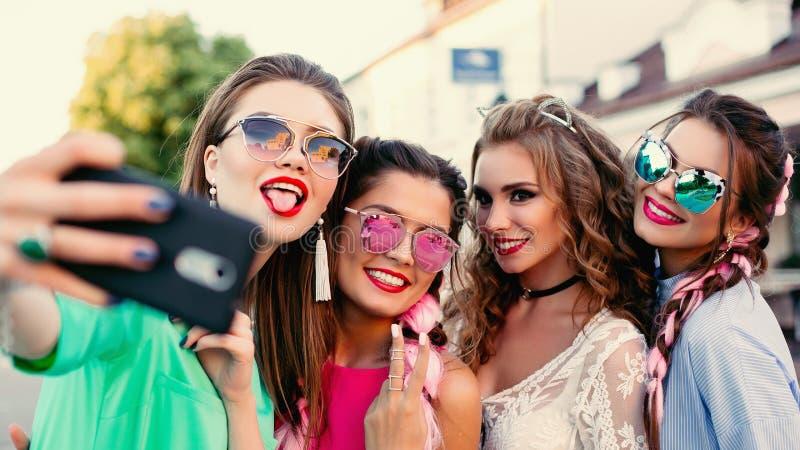 Quattro alla moda e le belle le migliori amiche in vetri, posanti fanno l'auto generale per le reti sociali, stile di vita, spend fotografie stock libere da diritti