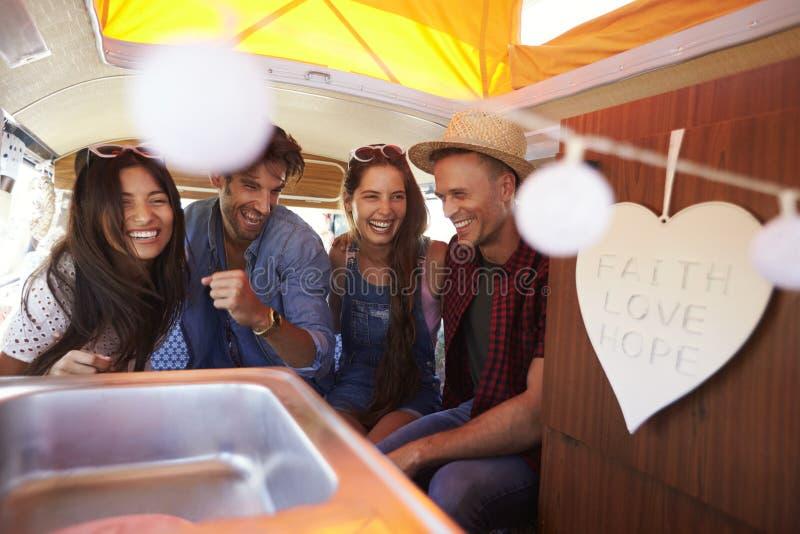 Quattro amici che ridono nella parte posteriore di un camper fotografia stock
