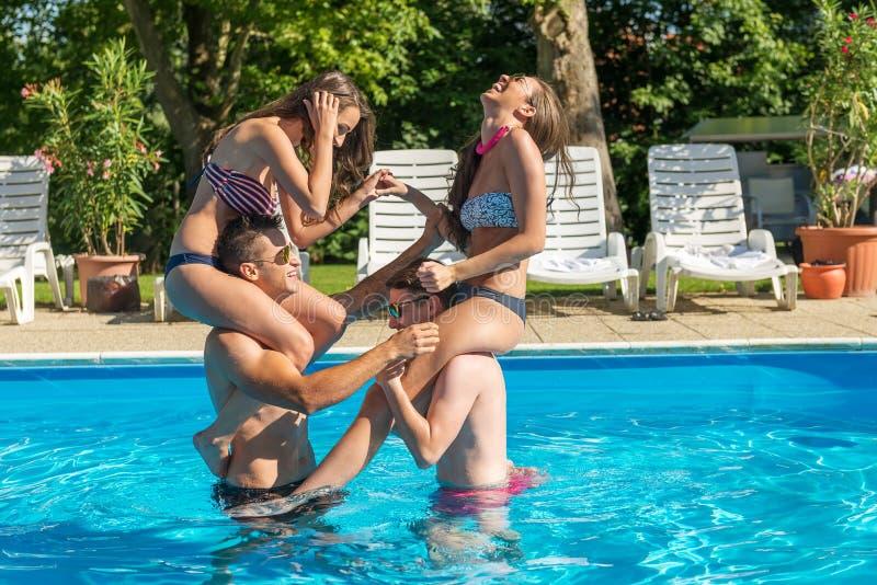Quattro amici divertendosi nella piscina immagini stock