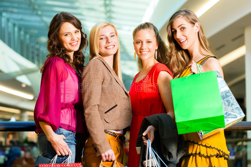 Quattro amici femminili che acquistano in un viale fotografia stock
