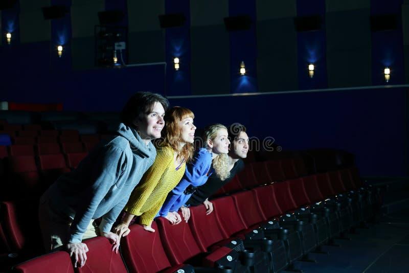 Quattro amici hanno peso sopra le parti posteriori delle sedie e dello sguardo allo schermo fotografia stock