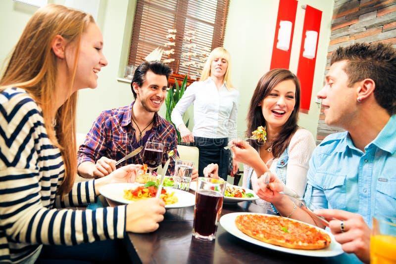 Quattro amici pranzando ad un ristorante fotografia stock