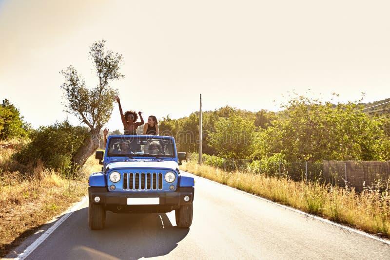 Quattro amici sulla strada in automobile aperta, stare di due donne fotografie stock