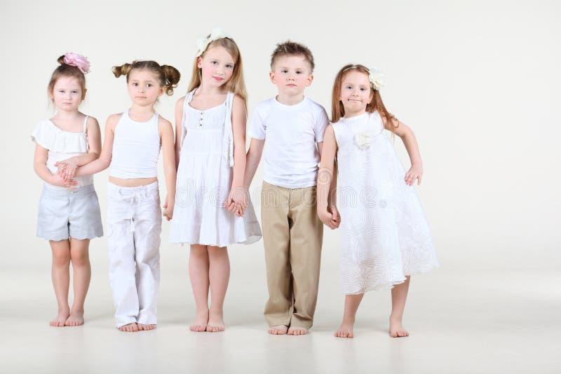Quattro bambine e ragazzo nei supporti bianchi dei vestiti fotografie stock