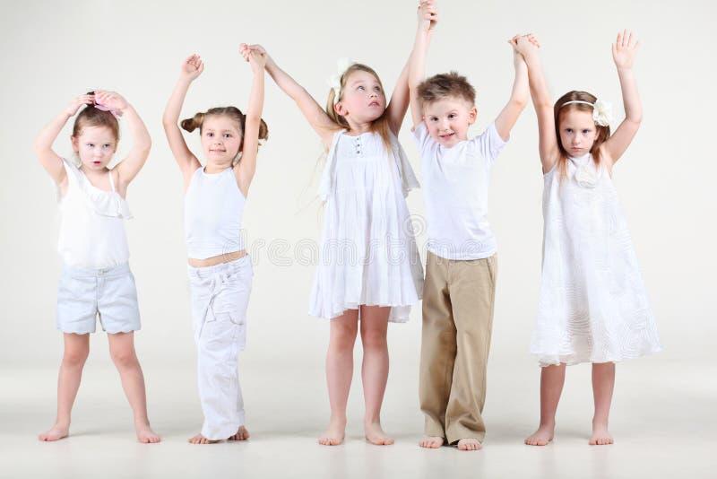 Quattro bambine sveglie ed una tenuta del ragazzo sulle mani su fotografie stock