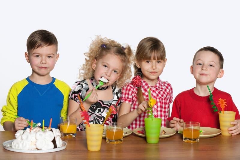 I bambini celebrano un compleanno alla tavola fotografia stock libera da diritti