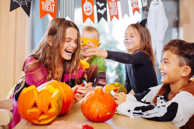 Quattro bambini che indossano Halloween costumes ridere fragorosamente durante il partito fotografie stock libere da diritti