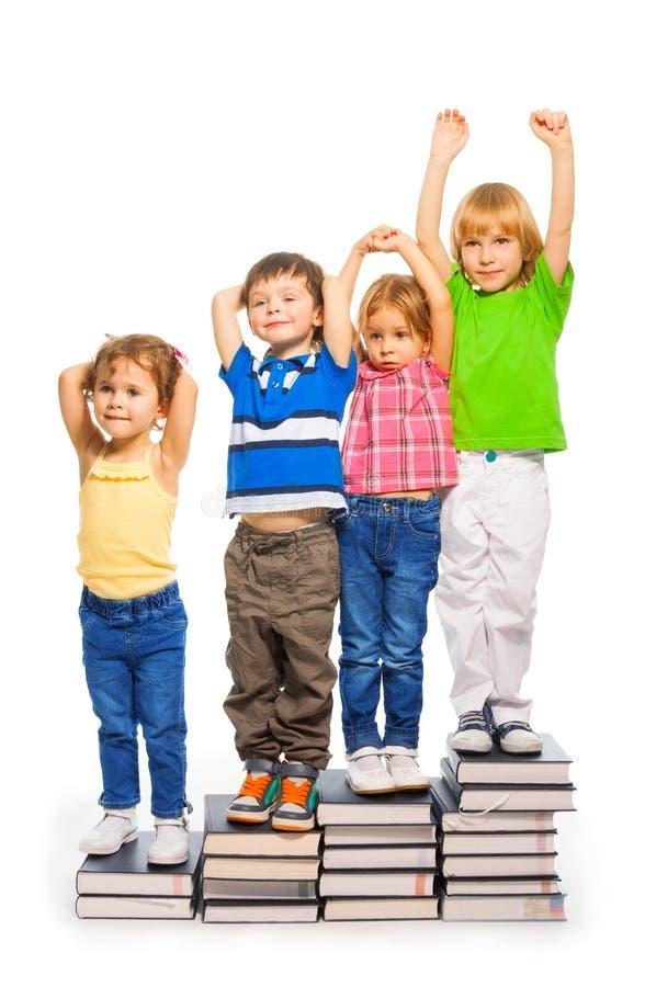 Quattro bambini che si siedono sui libri fotografia stock libera da diritti