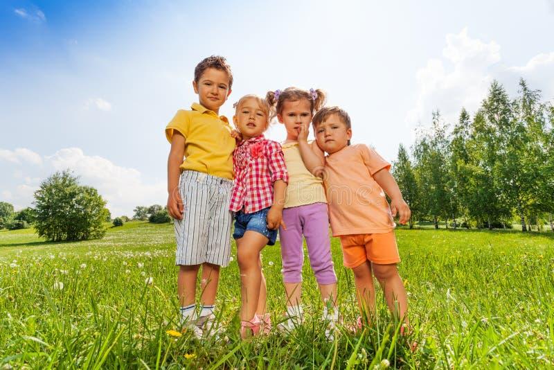 Quattro bambini che stanno vicino ad a vicenda in prato fotografia stock libera da diritti